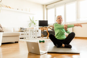 Senior woman exercising at home using an online trainer service.