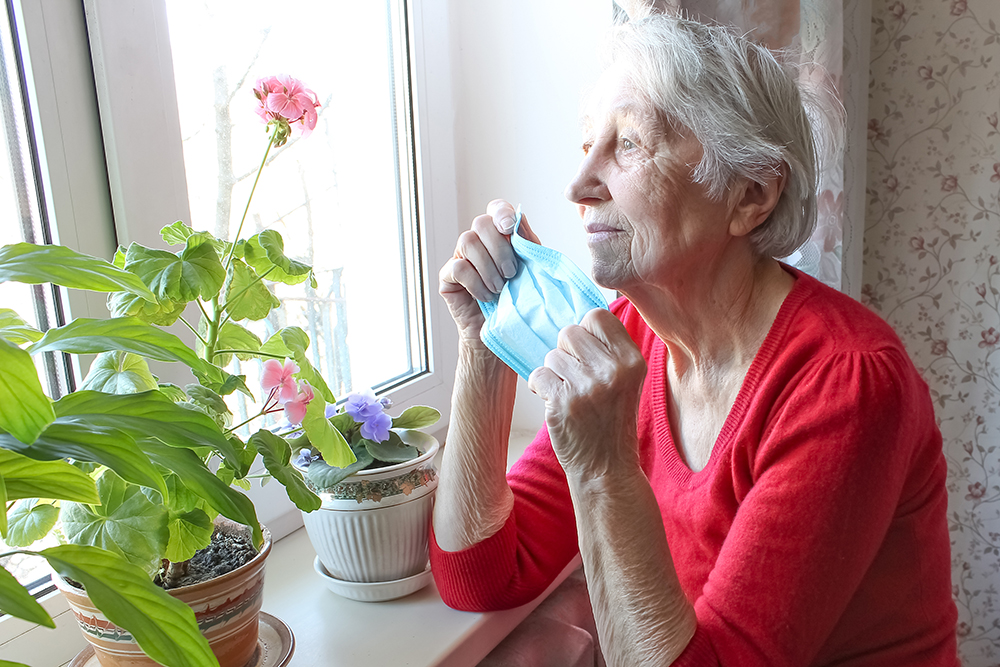 senior lady holding mask looking longingly out window