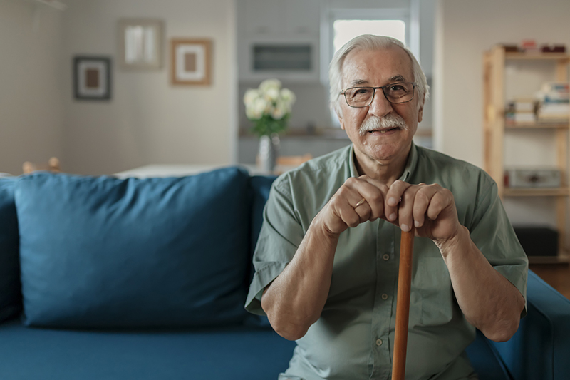 happy senior man smiling at home while holding walking cane