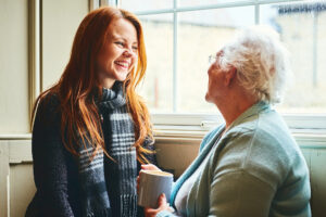 Young caregiver talks with senior woman about in-home care solutions
