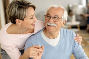 happy-caregiver-helping-man-with-parkinsons